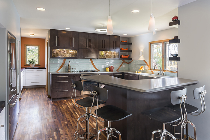 Modern kitchen with dark stained birch cabinets and counter with barstools