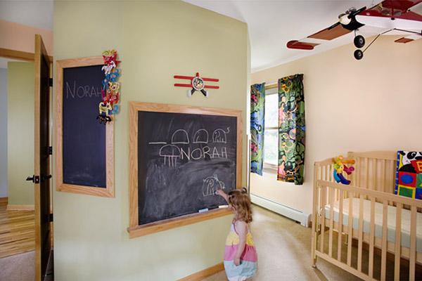 Little girl's bedroom with three chalkboards of differing heights on the wall
