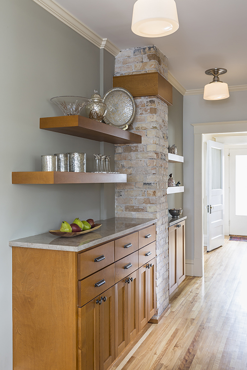 Cabinets and open shelving flank exposed brick chimney in remodeled kitchen