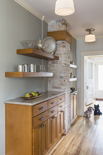 Cabinets and open shelving flank exposed brick chimney in remodeled kitchen with two small dogs
