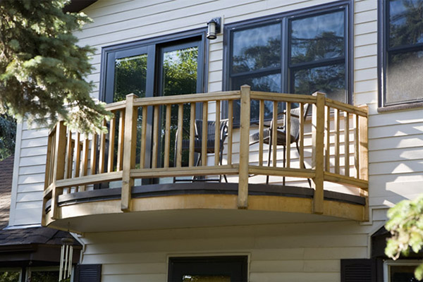 Detail shot of wooden balcony on front of house with vinyl siding