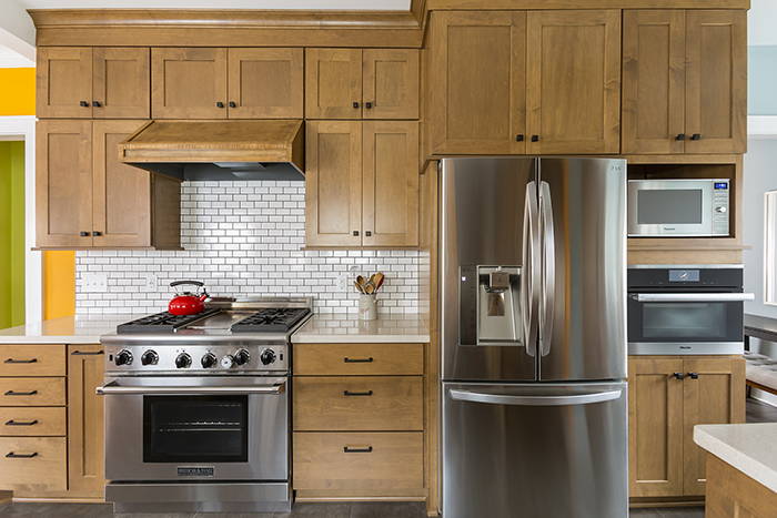 Birch kitchen cabinets surrounding stainless steel appliances and white subway tile backsplash