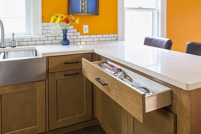 Utensil drawer in kitchen is short to accommodate space for barstools on other side of cabinet