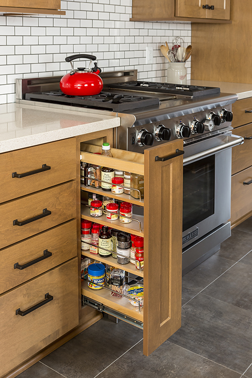 Vertical pull-out pantry drawer next to stove in kitchen